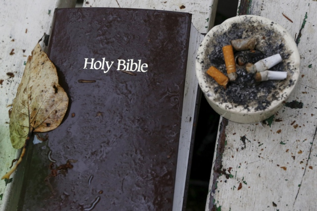 """A bible and ashtray filled with cigarettes are seen at SHARE/WHEEL Tent City 4 outside Seattle, Washington October 9, 2015. SHARE and WHEEL describe themselves as self-organised, democratic organisations of homeless and formally homeless people which run several self-managed tent cities. At homeless encampments from Seattle, Washington state to Las Cruces, New Mexico, residents live away from the dangers of life on the streets, saying the stability helps them work towards their goals. Despite a shortage of affordable housing for the poor and budget constraints on social welfare programmes, many U.S. cities have clamped down on tent cities in the past few years.  REUTERS/Shannon Stapleton PICTURE 15 OF 35 - SEARCH """"STAPLETON TENTS"""" FOR ALL IMAGES - RTX1Z3IV"""